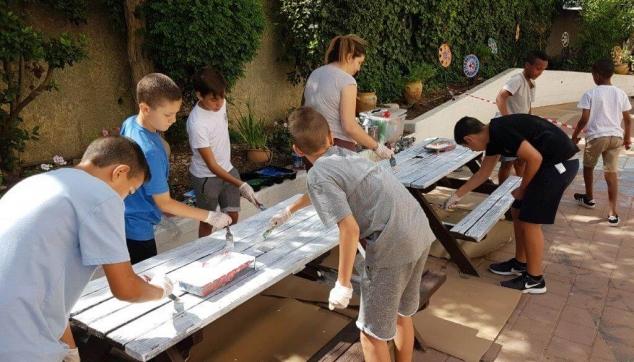 תלמידים צובעים שולחנות בית ספרם