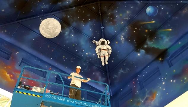 ציור קיר על התקרה של חלל עם אסטרונאוטים